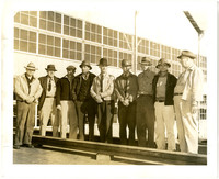 Yard Superintendents - nine men stand in a line outside a large warehouse or factory