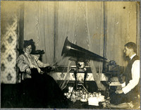 A woman sits in front of a phonograph while a young man sits behind it beside several cylinder records