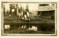 Movie set with film crew near cabin and pond in woods