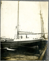 Single masted wooden sailboat with sailor climbing rope ladder up mast
