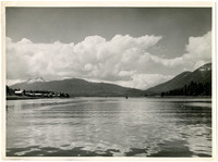 View across water of bay or inlet with village on left, mountains in distance