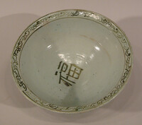 Bowl decorated in underglaze green floral sprays on exterior, the interior with character in center and scroll band ar rim
