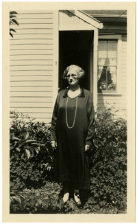 A woman wearing a long dress and long strand of pearls poses in garden of residence