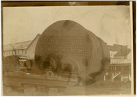 The boiler box of a very large steam engine rests on ground with wharf and warehouses in background