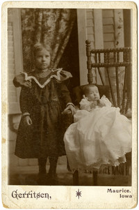 K. Bruins - Portrait of girl standing next to baby in chair