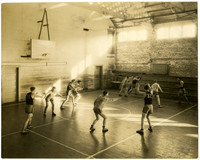 Basketball game in gymnasium with light pouring in through upper windows