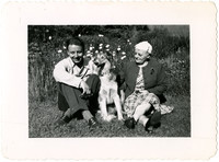Pianist Gunnar Anderson and his mother sit in grass with  a Collie dog between them, wildflowers in background