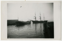 View from water of a three-masted sailing ship and a cargo or fishing vessel near dock