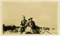 A woman and man sit atop rocks on alpine ridge