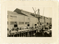 View from deck of ship as it approaches pier with large crowd of people awaiting its arrival