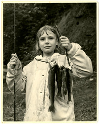 A girl with fishing pole holds up her day's catch of four fish strung on a stick