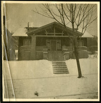 Street view of front of home with steps leading from sidewalk to large front porch of craftsman-style home on a snowy day