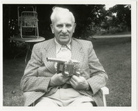 Unidentified white-haired man sitting outdoors on a folding metal lawn chair, holding a miniature replica of a cannon