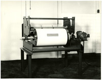 Motorized machine with large white drum or roller at center