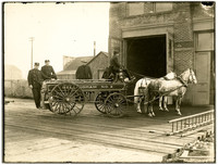 Bellingham No.2 fire wagon stands with two hitched horses outside open doors of fire house with three men and the driver