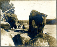 Huge, water worn boulders stand along the shore of a bay.