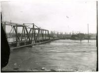Swollen Nooksack river flows under railroad bridge