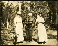 A man holding his hat stands between two women while they share a laugh, standing on a forest lane