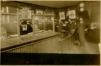 Three men in suits stand in lobby of bank or post office with teller window