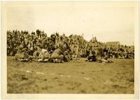 Fairhaven High School football team resting at Battersby Field during game with bleachers full of spectators in background