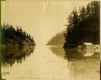 Water scene with rocky, forested shorelines on either side, small boathouse on right