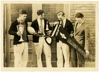 Four young men pose with trophies and pennant