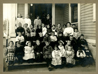 Primary students and their teacher pose on steps of school
