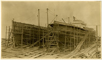 Boatbuilding operation showing two boats under construction surrounded by scaffolding, ramps and lumber