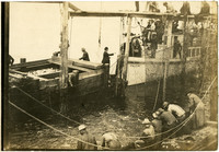 "Men tend to fishtrap lines while passenger ferry ""Falcon"" attaches to fishing barge"