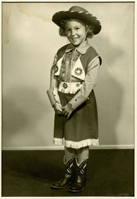 Young girl poses in cowgirl outfit with boots and hat