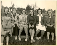 Six high school girls sit in a row outdoors