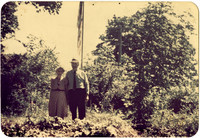 Elderly couple stands in garden with flagpole in background