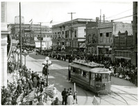 A trolley moves down the center of Holly Street, Bellingham, Washington, as crowds gather on sidewalks