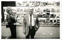 Galen Biery stands smiling in front of a wall of photographs, with his cousin Evelyn Montgomery Hinds Von Bargen to the left