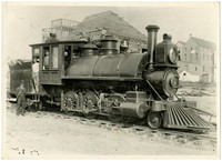 Train locomotive with three men standing in or next to cab