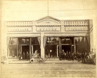 Storefront of Underwood & Minturn selling hardware, stoves, tinware, with several men in suits standing in front of both doorways, goods and merchandise on display in windows