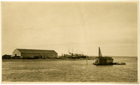 View across water of warehouse or cannery with several beached cannery tenders