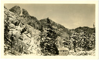 Stone cabin at base of snowy Mt. Herman