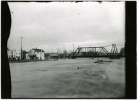 Flooding waters of Nooksack river rush forward with railrad bridge and buildings of Ferndale, WA, in background