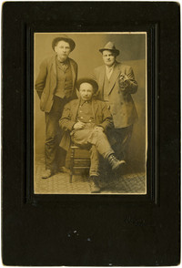 Two men standing, one man seated, pose for portrait