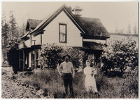Man and woman holding baby stand in tall grass with two story house of Berthusen homestead behind them, forest in background