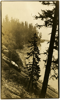 View from above of steam train traveling along railway on mountainside next to shore