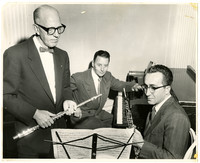 Three men in suits looking at a music score, one, standing, holding a flute; one seated, holding a clarinet; and one, seated at a piano