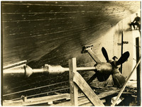Man stands behind giant propeller on hull of ship under construction