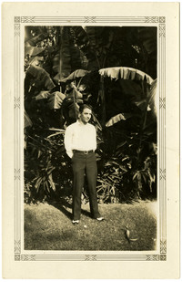 Unidentified man poses standing in front of palm trees