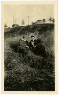 Two men reclining on a grassy slope