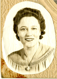 Oval shaped cut-out head shot of smiling woman with dark, wavy hair