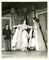 Theatrical stage scene with two women and one man in costumes during performance