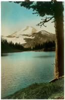 hand-tinted view of snow-covered Mt. Baker with a lake in the foreground.