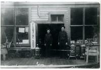 George Eliott with son Carl Curtis Elliott stand in doorway of Plumbing Shop